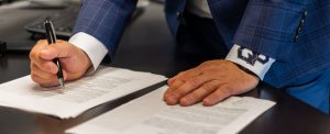 Quiet Professionals person signing a document