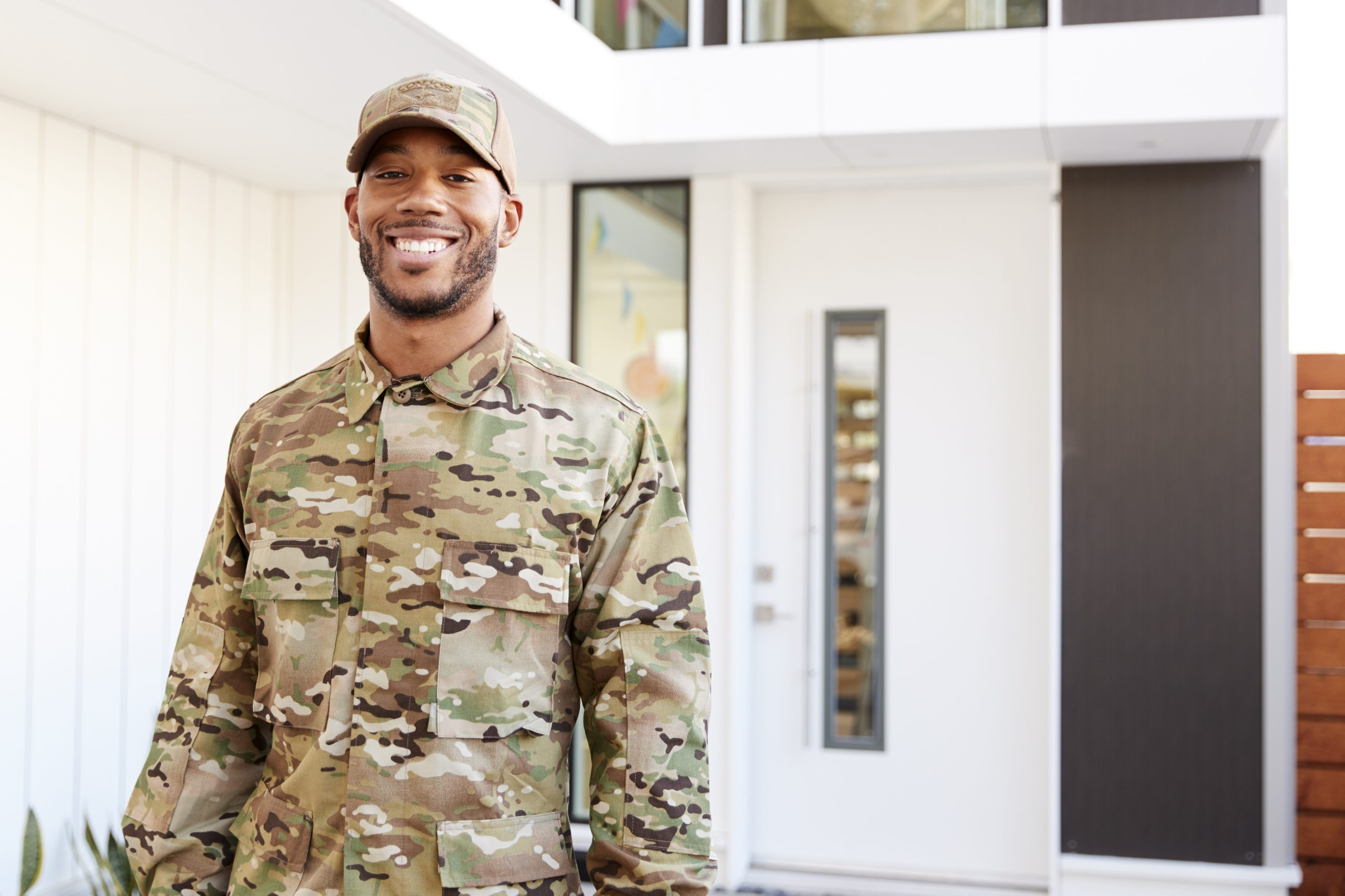 Male wearing camouflage smiling outside an office building
